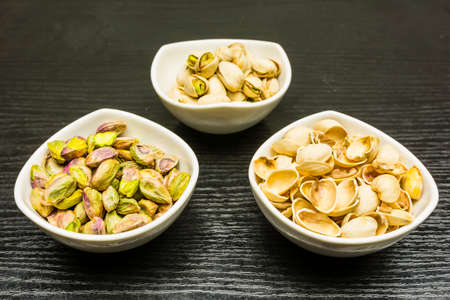 Shelling pistachio nuts on a wooden table. Whole, nutshell and peeled pistachios in bowls.