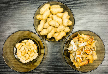 Shelling peanuts, nutshell in a bowl and clean peanuts on the plate. View from above.