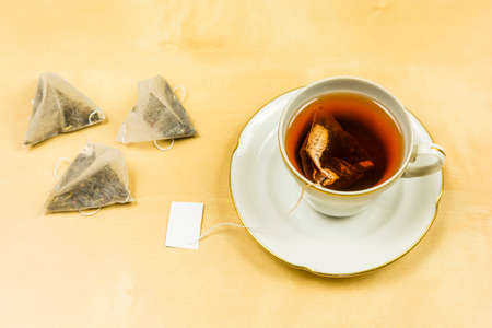 On the table, a porcelain cup with freshly brewed tea from a bag. Stock Photo