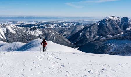Witow, Poland - March 22, 2018: Mountainous trek in the snow with a wide ridge. Hiker, while descending the snow-covered mountain ridge, admire the lowlands and the surrounding mountain peaks.