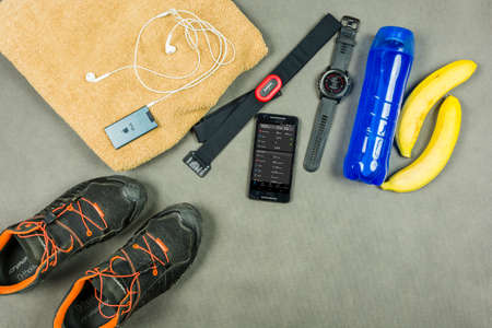 Niedomice, Poland - June 08, 2018: Runner training equipment. Heart rate monitor (Garmin), an isotonic drink, bananas, a towel, an iPod with dry jackets (Apple) and running shoes (Dynafit). Editorial