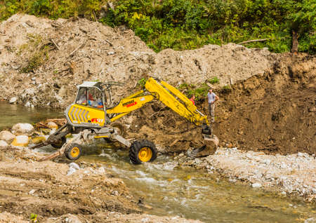 Pribylina, Slovakia - October 14, 2018: Forest digger Menzi Muck A91 in the river during earthworks.