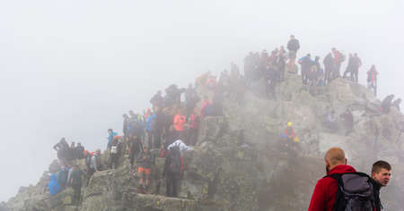 Palenica Bialczanska, Poland - September 08, 2018: Crowds of tourists in the mist on the top of Rysy. Tatra Mountains.