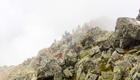 Palenica Bialczanska, Poland - September 08, 2018: Despite the bad weather, crowds of tourists on the top of Rysy. Tatra Mountains.