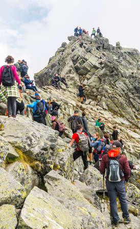 Palenica Bialczanska, Poland - September 08, 2018: Crowds of tourists on the top of Rysy. Tatra Mountains.