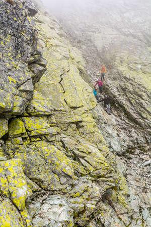 Strbske Pleso, Slovakia - September 02, 2018: A mountain guide bringing customers to the gully after climbing the summit - Wysoka (Vysoka) Publikacyjne