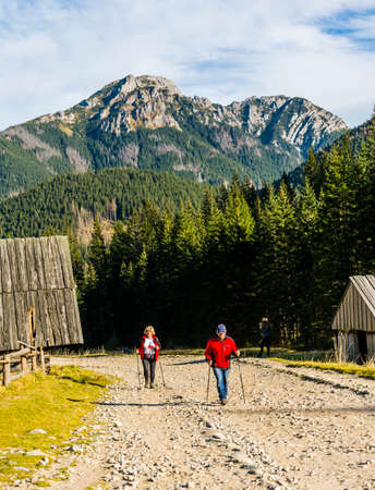 Witow, Poland - November 10, 2018: Pensioners on the trail. A pair of tourists with trekking poles walking along a road that runs along a valley in the mountains. A beautiful peak in the background.