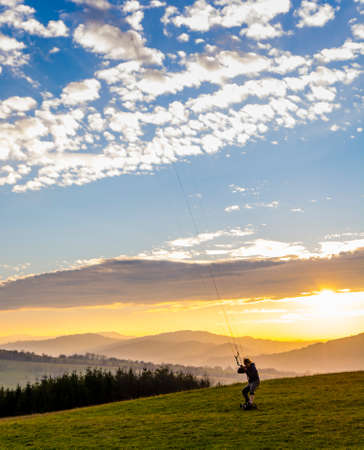 Wegierska Gorka, Poland - November 11, 2018: Kite landboarding, boy while driving on skateboard with large pneumatic wheels and foot-straps. In the background of the mountains with the setting sun. Publikacyjne