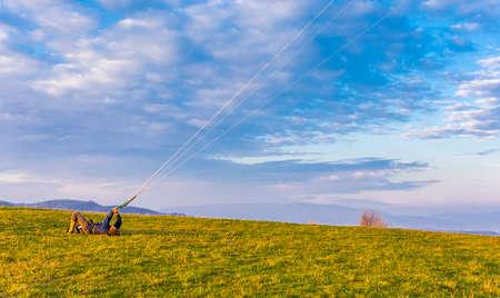 Wegierska Gorka, Poland - November 11, 2018: Land kiteboarding - Landboard rider keeps the control bar from controlling the kite lying down after falling.