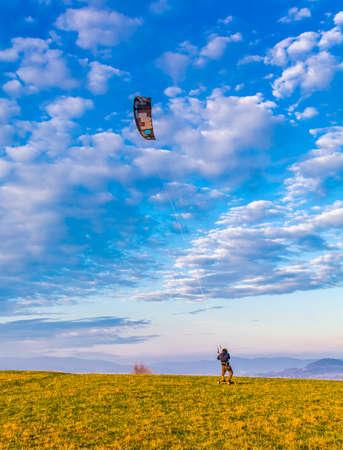 Wegierska Gorka, Poland - November 11, 2018: A kite landboarder in action at sunset. The boy uses a strong wind to ride.