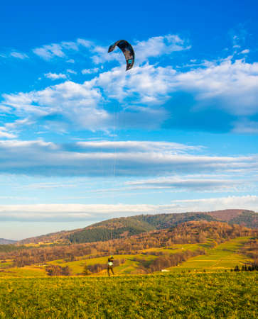 Wegierska Gorka, Poland - November 11, 2018: Land kiteboarding - girl in a helmet is training a ride in a clearing in the mountains at sunset.