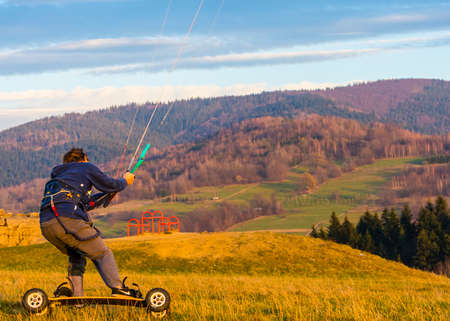 Wegierska Gorka, Poland - November 11, 2018: Landboard rider on board with large pneumatic wheels and foot-straps uses a bar with lines to control the kite, attached to a harness.