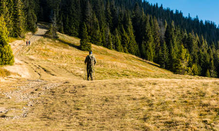 Ujsoly, Poland - November 11, 2018: A man wandering along a trail with a backpack and trekking poles.