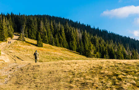 Ujsoly, Poland - November 11, 2018: A weekend trip of a mountainless man with a backpack and trekking poles.