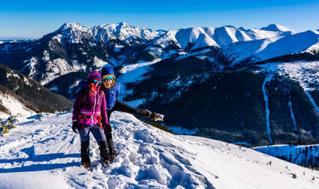 Witow, Poland - January 07, 2020: Happy women (tourists) in sunglasses and warm clothes on a frosty sunny day during a winter trip in the mountains.