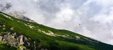 Tatranska Polianka, Slovakia - September 12, 2020: Paragliding - Paragliders flying over a mountain slope. Tatra Mountains. Publikacyjne