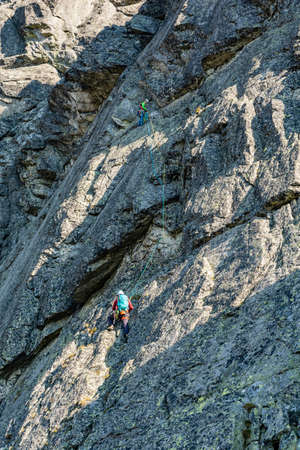 Strbske Pleso, Slovakia - September 14, 2020: Mountain climbing in the Tatra Mountains - Partner while belaying her climbing partner with anchor. Publikacyjne