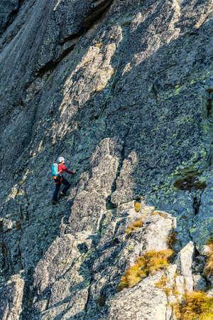 Strbske Pleso, Slovakia - September 14, 2020: Mountain Climbing - A climber climbs with an overhead belay.