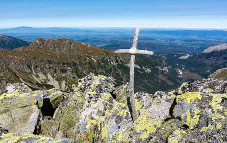Symbolic small wooden cross on top of the mountain. A cross made of sticks glued with a medical plaster.