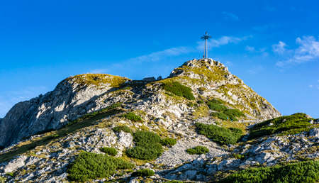 Cross at the top of Giewont. A popular tourist destination during the summer holidays. View on a beautiful sunny summer day.