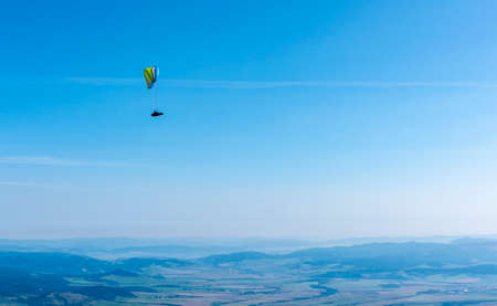 Tatranska Lomnica, Slovakia - September 15, 2020: Paragliding - A paraglider flying high above the valley on a beautiful sunny day. Publikacyjne