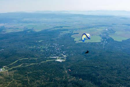 Tatranska Lomnica, Slovakia - September 15, 2020: Paragliding - paragliders flying over Tatranska Lomnica. Publikacyjne