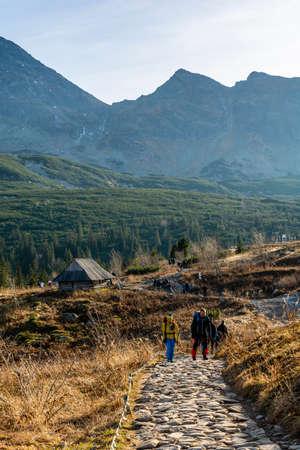 Zakopane, Poland - November 11, 2020: Autumn trip to the mountains. Tourists on the trail marked by Hala Gasienicowa in the Gasienicowa Valley in the Tatra Mountains. Poland.
