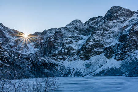 A solar star emerging in a mountain pass in the main ridge of the Tatra Mountains. Early winter view from the Morskie Oko lake (Eye of the Sea), Poland.