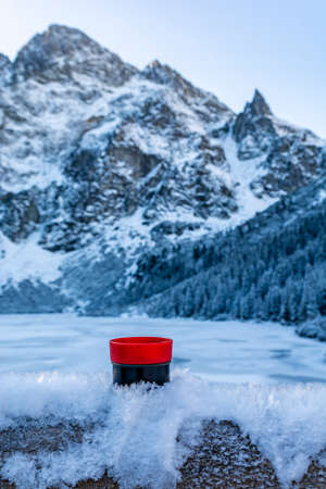 A red and black   cup with a hot drink (tea) placed in the frozen snow against the background of mountain peaks near the Morskie Oko Lake. Tatra Mountains, Poland. Zdjęcie Seryjne