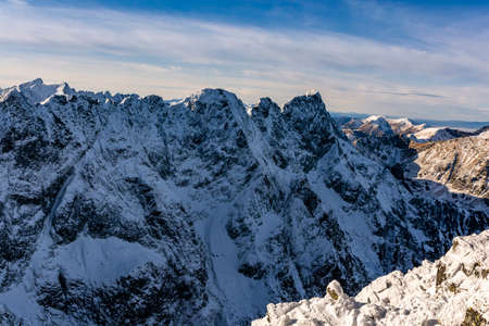 A fragment of the Main Ridge of the Tatra Mountains in the snow rime on a beautiful sunny and frosty day. Among the peaks, among others, Mieguszowiecki Summits.