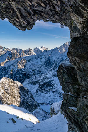 View from the cave on the mountain ridges and the valley in a snowy scenery. Zdjęcie Seryjne