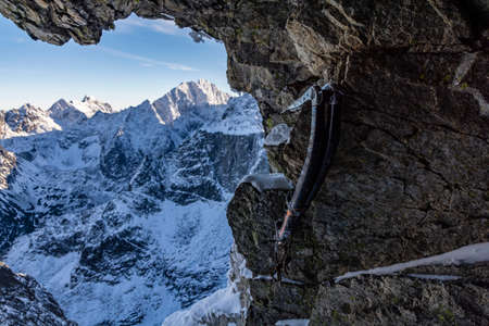 Two technical ice axes suspended on a rock in a cave overlooking the snow-covered mountains.