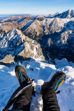 Technical mountain boots with crampons on the climber's legs and two ice axes with a beautiful mountain landscape in the background. While resting after hiking on the summit.