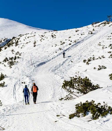 Zakopane, Poland - March 02, 2021: Sport is health. A couple of friends during a mountain hiking trip to Kasprowy Wierch in winter. Tatra Mountains, Poland.