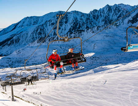 Zakopane, Poland - March 02, 2021: Sport is health. A pair of skiers going by Gasienicowa chairlift - Polish Cable Railways, to the top of Kasprowy Wierch. Tatra Mountains.