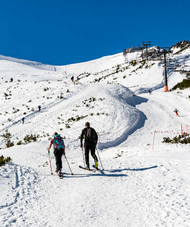 Zakopane, Poland - March 02, 2021: Sport is health. A pair of skiers chose to ski to the top of Kasprowy Wierch, instead of going by a nearby chairlift. Tatra Mountains, Poland. Publikacyjne