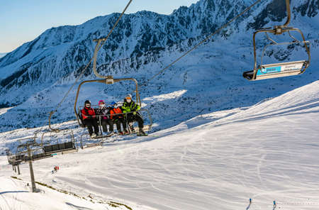 Zakopane, Poland - March 02, 2021: Recreational skiing during the Covid-19 pandemic. A family of skiers wearing protective masks going by chairlift to the top of Kasprowy Wierch. Tatra Mountains.