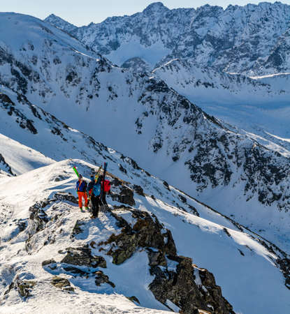 Zakopane, Poland - March 02, 2021: Ski touring, three skiers with skis attached to their backpacks on a rocky ridge. A break in the trip for a commemorative photo.