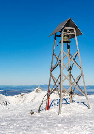 Zakopane, Poland - March 02, 2021: One of the symbols of the Tatra Mountains, ie the bell at the top of Kasprowy Wierch (Kasprov vrch), in the background another symbol of the Tatra Mountains, Giewont peak.