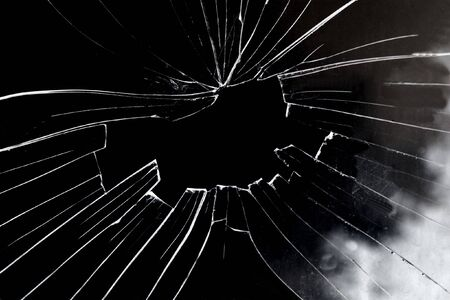 Broken glass hole with black background