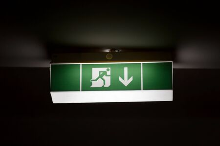 instruct: Emergency exit sign glowing in the dark