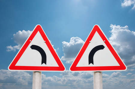 contradict: Turning road traffic signs showing opposite directions Stock Photo