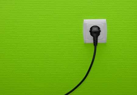 Electric outlet on green wall with cable plugged Stock Photo