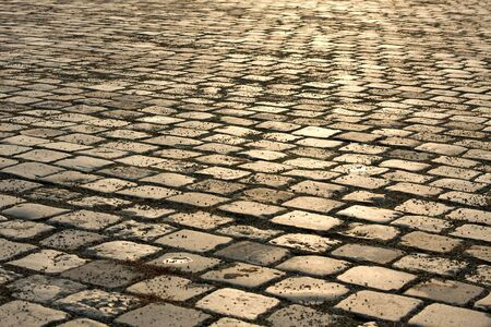 Old stone pavement reflecting sunset light photo