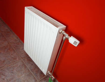 Radiator against red wall Stock Photo - 4581730