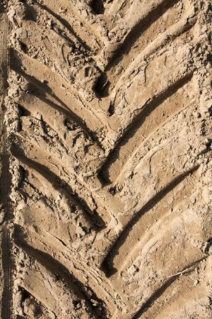 Tractor trail closeup on the soil photo