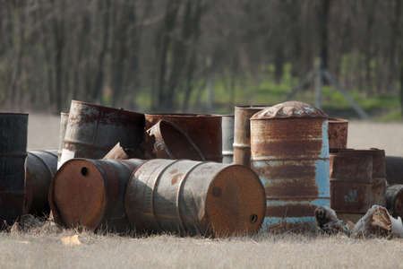 disposed: Disposed empty, rusty oil barrels in a field Stock Photo