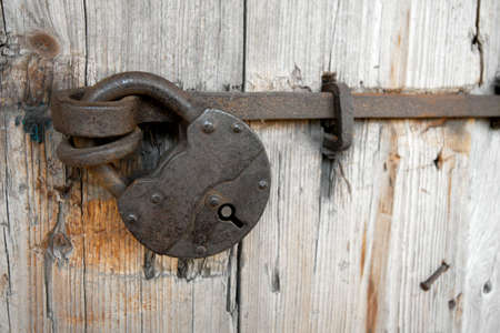 Old padlock on a wooden door Stock Photo