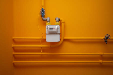 Pipes and gas-meter on orange wall photo