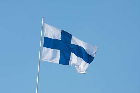 finland�s: Fin�s bandera nacional contra el cielo azul claro Foto de archivo